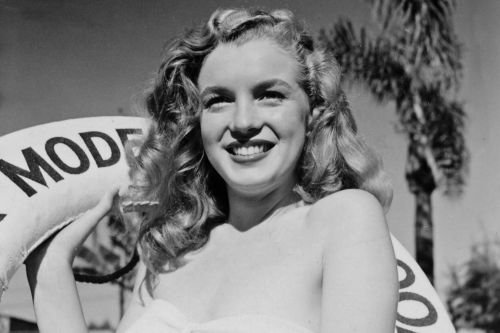 ONE-USE-ONLY-A-smiling-Norma-Jeane-holding-the-Blue-Book-Models-life-ring